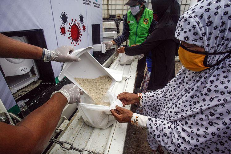 Relawan menuangkan beras gratis di ATM beras keliling Bogor Gercep di Desa Bojong Nangka, Gunung Putri, Bogor, Jawa Barat, Kamis (23/4/2020). Kegiatan tersebut guna meringankan beban ekonomi warga terdampak COVID-19 di wilayah Kabupaten Bogor.