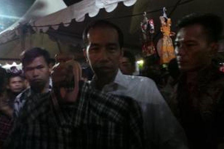 Gubernur DKI Jakarta Joko Widodo membeli kemeja di Kaki Lima Night Market, Jakarta, Sabtu (5/10/2013) malam.