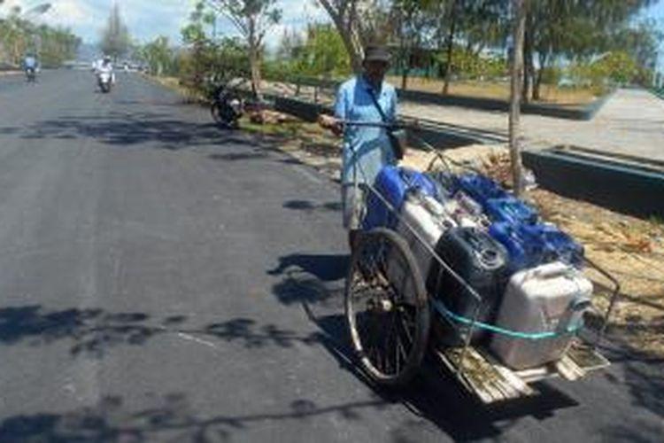 La Mbolode (54), warga Kelurahan Lanto, Kecamatan Betoambari Kota Baubau, saat berkeliling berjualan air bersih keliling dengan menggunakan gerobaknya.