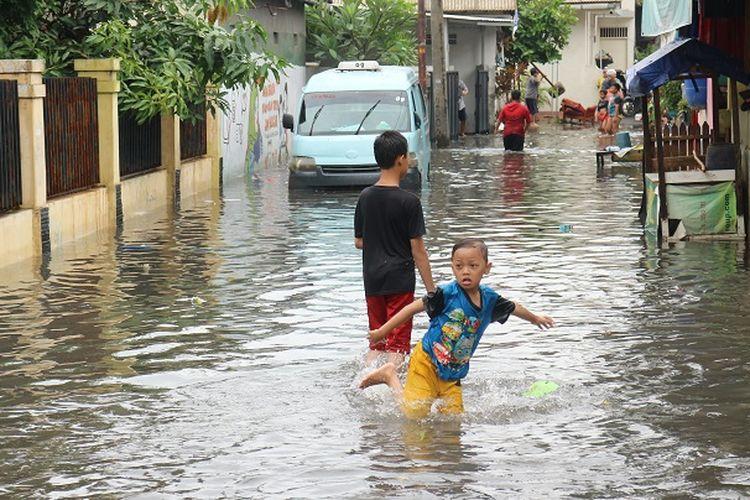 Anak-anak memanfaatkan air banjir untuk bermain di sekitaran Kali Sekretaris, Kebon Jeruk, Jakarta Barat, Rabu (1/1/2020).