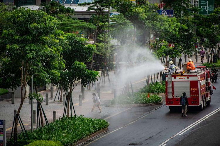 Petugas Damkar menyemprotkan cairan disinfektan di kawasan Jalan Sudirman, Jakarta, Minggu (22/3/2020). Pemprov DKI Jakarta melakukan penyemprotan fasilitas umum menggunakan cairan disinfektan di lima wilayah DKI Jakarta untuk mencegah penyebaran virus Corona atau COVID-19.