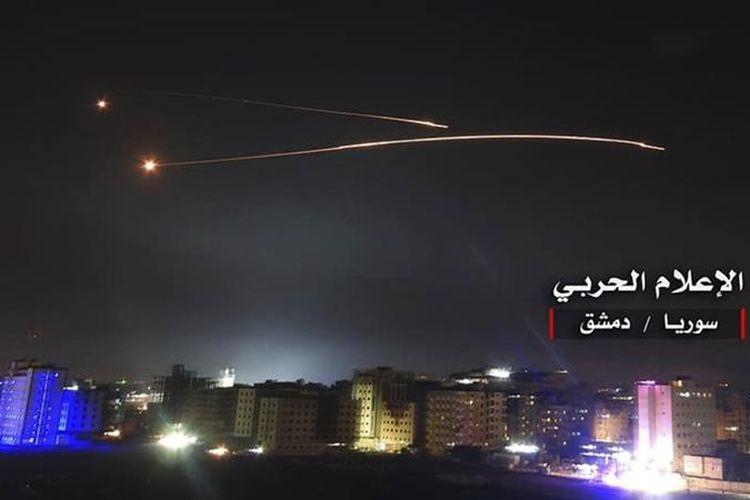 Foto menunjukkan dua rudal yang berasal dari Israel dan Suriah terbang di langit malam dekat ibu kota Damaskus. Suriah menyatakan serangan udara Israel menghantam gudang amunisi dan melukai tiga orang prajurit.