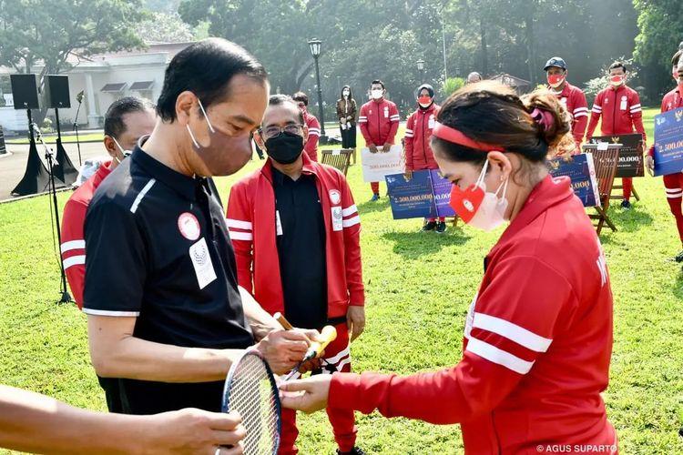 Presiden Joko Widodo menandatangani raket Leani Ratri Oktila (atlet para-badminton Indonesia) di Istana Merdeka, Jakarta, Jumat (17/9/2021).