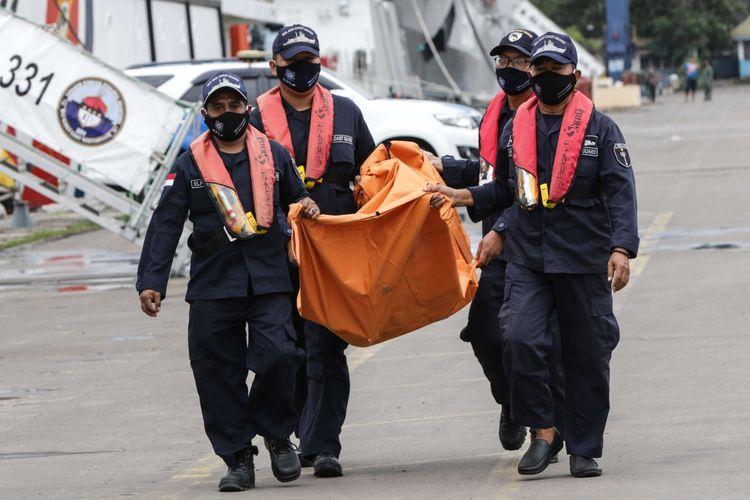Petugas membawa serpihan pesawat Sriwijaya Air SJ 182 rute Jakarta - Pontianak yang jatuh di perairan Kepulauan Seribu di Posko SAR Sriwijaya Air, Dermaga JICT II, Tanjung Priok, Jakarta, Rabu (13/1/2021).
