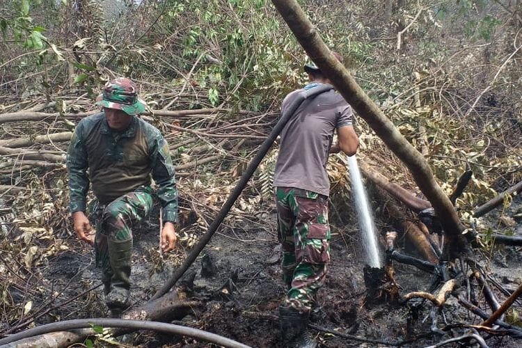 Hati ketiga petugas gabungan dari Manggala Agni, TNI dan kepolisian melakukan pemadaman api kebakaran hutan dan lahan milik PT Pertamina RU II di Kelurahan Bukit Datuk, Kecamatan Dumai Selatan, Kota Dumai, Riau, Sabtu (30/3/2019).