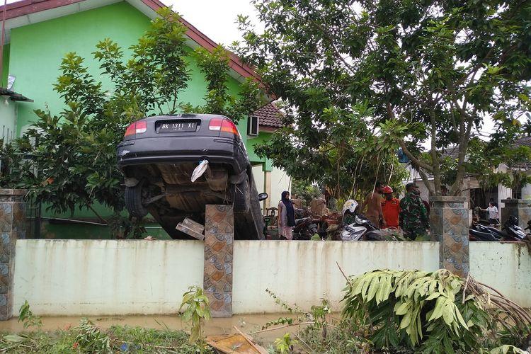 Posisi mobil milik Defri Solihin tersangkut di pagar. Pohon rambutan menghalanginya saat terjadi banjir di perumahan De Flamboyan di Kelurahan Tanjung Selamat, Kecamatan Medan Tuntungan pada Kamis malam hingga Jumat dini hari (4/12/2020).