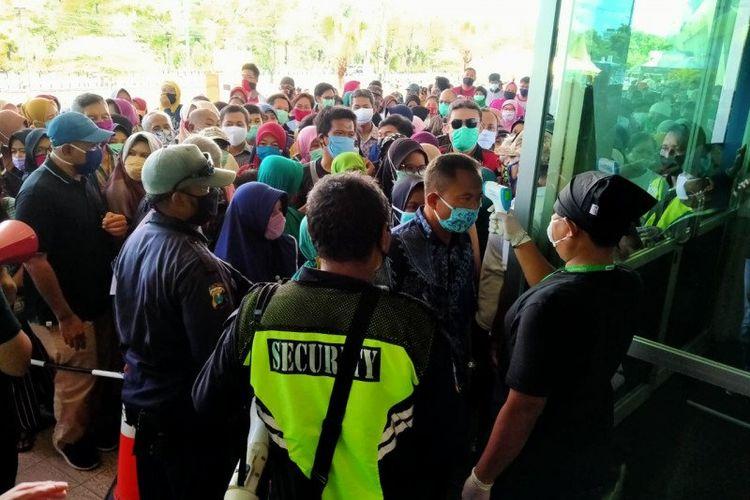 Petugas saat mengecek suhu tubuh warga yang mengantre untuk membeli sembako murah pada Lumbung Pangan Jatim di JX International Surabaya, Selasa (21/04/2020) pagi.