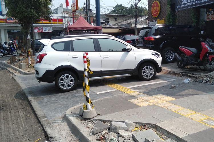 Mobil dan sepeda motor parkir di trotoar Jalan Kemang Raya, Mampang, Jakarta Selatan, Jumat (23/8/2019). Trotoar di kawasan Kemang sedang direvitalisasi.