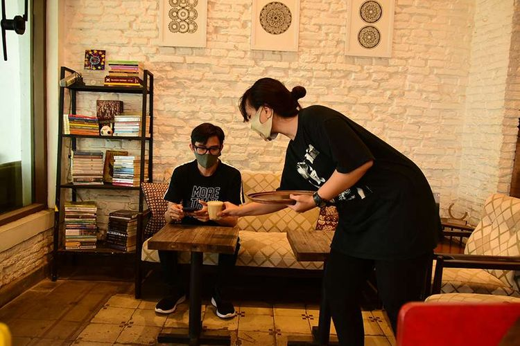 Pengunjung menikmati kopi gratis di salah satu kedai kopi di Jalan Veteran, Bandung, Jawa Barat, Rabu (30/6/2021). Kedai kopi tersebut menggelar 'Vaccine Free Coffee', program bagi-bagi kopi gratis yang hanya berlaku untuk hari ini saja, Rabu, untuk mengapresiasi pengunjungnya yang sudah menjalani vaksinasi Covid-19.