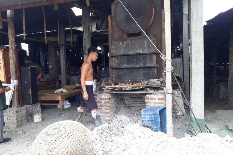 Pekerja pabrik tahu di Desa Tropodo, Kecamatan Krian, Sidoarjo, Jawa Timur, memasukkan limbah plastik impor sebagai bahan bakar pengganti kayu, Selasa (26/11/2019).