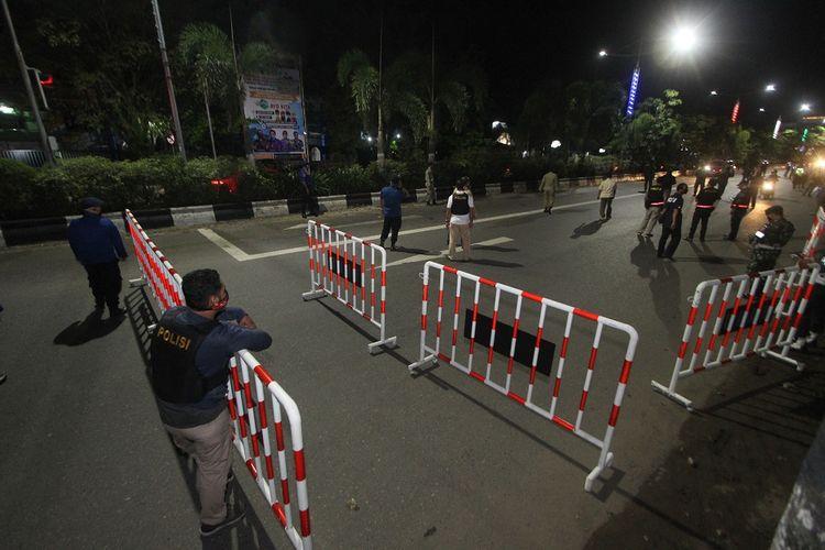 Petugas gabungan melakukan penyekatan jalan masuk ke dalam kota di perbatasan Kota Banjarmasin, Kalimantan Selatan, Jumat (24/4/2020) malam. Saat pemberlakuan jam malam untuk mendukung Pembatasan Sosial Berskala Besar (PSBB) di Kota Banjarmasin, dilakukan penyekatan jalan masuk menuju dalam kota dengan akses terbatas melalui pemeriksaan oleh petugas guna mencegah penyebaran COVID-19. ANTARA FOTO/Bayu Pratama S/wsj.