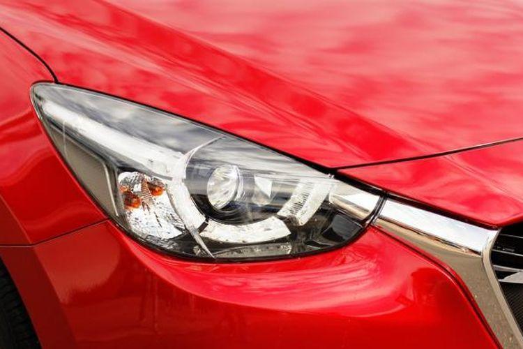 Lampu depan Mazda2 yang didesain seperti mata cheetah, dengan empat LED di sekeliling lampu utama.