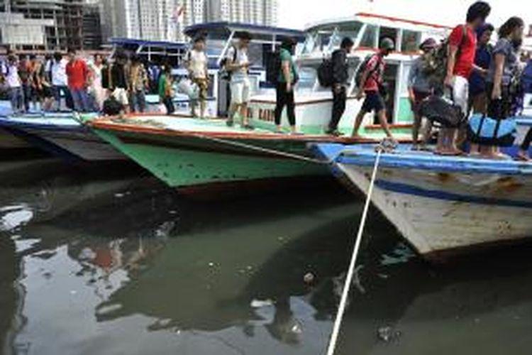 Wisatawan yang selesai berlibur di Kepulauan Seribu turun dari kapal yang bersandar di Dermaga Muara Angke, Jakarta, Minggu (6/1/2013).