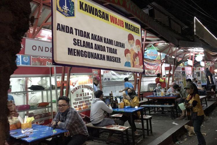 Spanduk Kawasan Wajib Masker di kuliner Bubur Ayam Barito, Kebayoran Baru, Jakarta, Selasa (7/7/2020) malam.