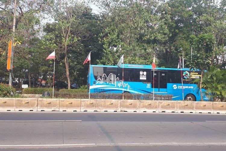Bendera negara peserta Asian Games menggunakan tiang bambu tampak terpasang di sepanjang Jalan Mayjen Sutoyo, Cawang, Jakarta Timur, Selasa (31/7/2018)