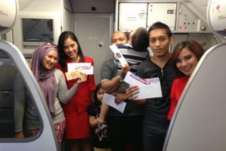 Awak kabin AirAsia Indonesia berfoto bersama para pemenang kuis berhadiah voucher belanja persembahan Singapore Tourism Board di dalam penerbangan perdana dari Makassar menuju Singapura.