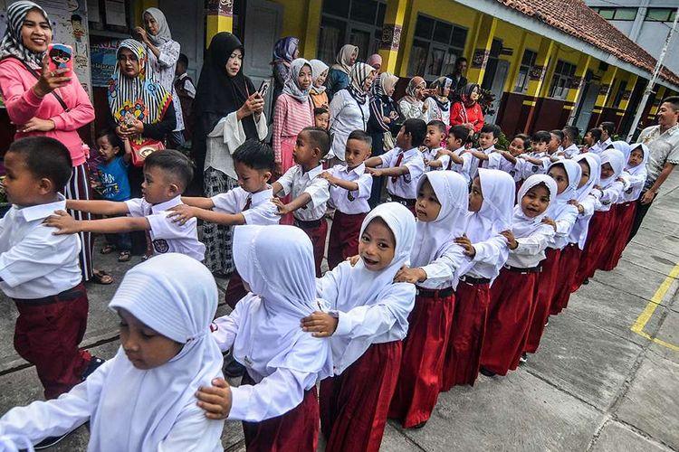 Siswa baru kelas satu Sekolah Dasar Negeri Pengadilan berbaris disaksikan para orangtua di Kota Tasikmalaya, Jawa Barat, Senin (15/7/2019). Hari pertama masuk sekolah tahun ajaran 2019-2020 dimulai serentak dan para orang tua siswa hadir mengantar anaknya untuk mengenal lingkungan sekolah serta berinteraksi dengan pihak sekolah dan guru.