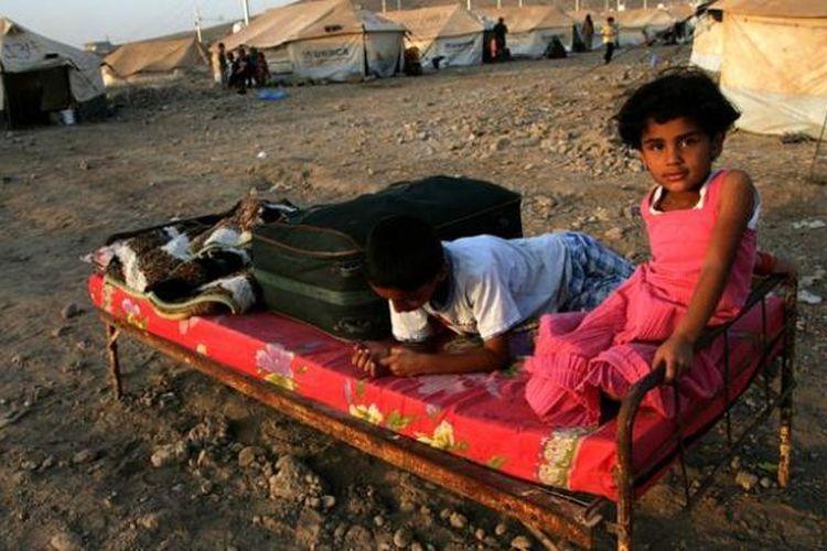 Dua orang pengungsi anak-anak Suriah, bermain di sebuah kamp pengungsi Suriah di dekat kota Arbil, Irak. PBB mengatakan sekitar satu juta anak-anak Suriah kini menjadi pengungsi di berbagai negara dan dua juta lainnya kehilangan tempat tinggal.