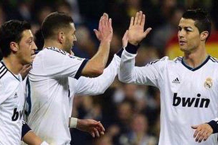 Penyerang Real Madrid dari Perancis, Karim Benzema (tengah), merayakan golnya dengan rekan-rekan seklubnya, gelandang Jerman Mesut Ozil (kiri), dan bomber dari Portugal Cristiano Ronaldo (kanan) saat berlaga melawan Athletic Bilbao dalam laga pekan ke-12 Liga BBVA di Stadion Santiago Bernabeu, Sabtu (17/11/2012). Madrid akhirnya menang 5-1.