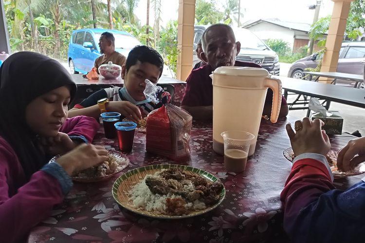 Keluarga Azam Mahat menbikmati hidangan di salah satu rumah yang disangkanya warung di Kelantan, Malaysia, pada 2 Januari