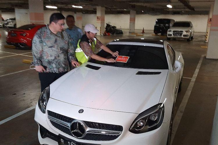 Petugas menempelkan stiker ke mobil mewah bermerek Mercedes yang pajaknya belum dibayar di Apartemen Regatta, Jakarra Utara, Kamis (5/12/2019).