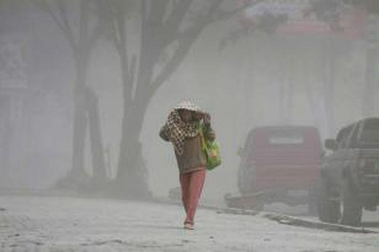 Warga berjalan di bawah hujan abu letusan Gunung Sinabung di Kabupaten Karo, Sumut, 17 September 2013. Gunung Sinabung meletus lagi pukul 12.03. Status gunung masih Siaga III.