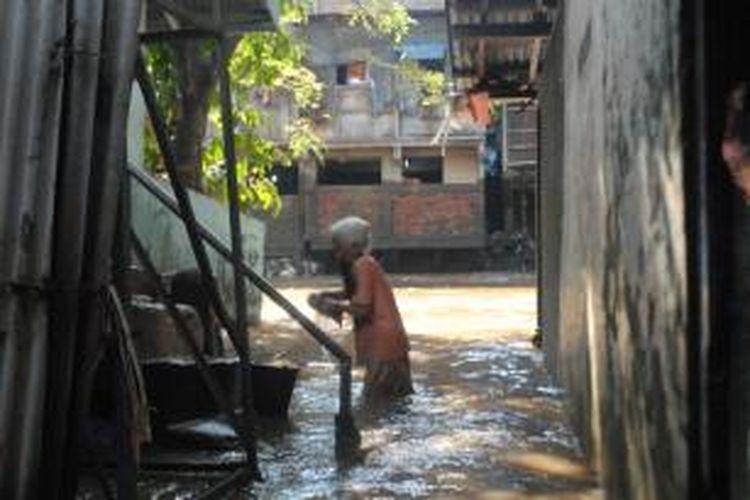 Seorang warga Kampung Pulo, Kampung Melayu, Jatinegara, Jakarta Timur, membersihkan rumah yang kotor akibat luapan air Kali Ciliwung, Selasa (23/7/2013).