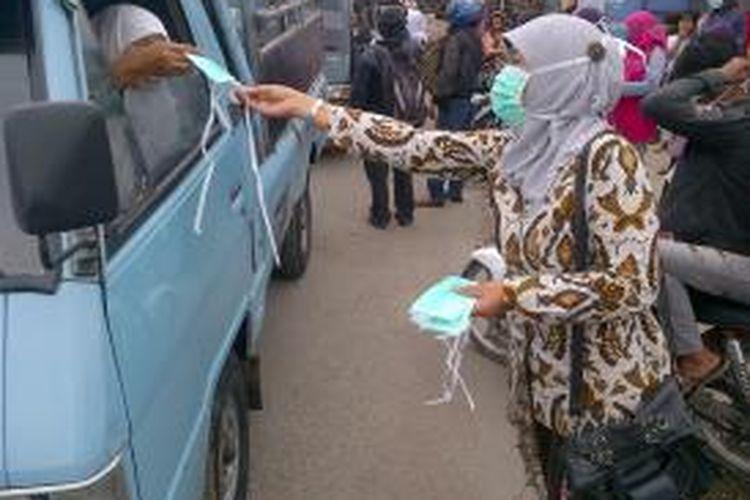 Salah seorang petugas dari Puskesmas Bumijawa Tegal, Jawa Tengah, membagikan masker kepada pengguna jalan mengantisipasi dampak abu vulkanik gunung Kelud, Jumat (14/2/2014).
