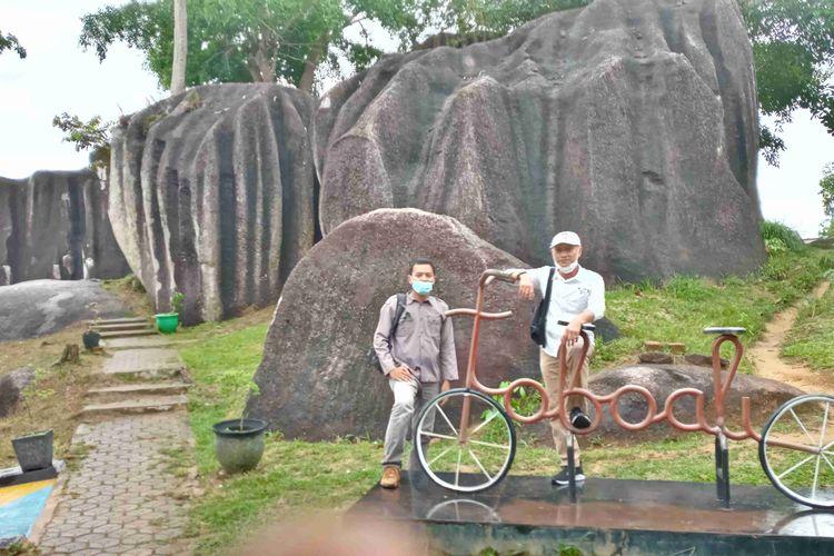 Pengunjung berpose dengan replika sepeda di gugusan batu belimbing, Toboali, Bangka Selatan, Rabu (23/6/2021).