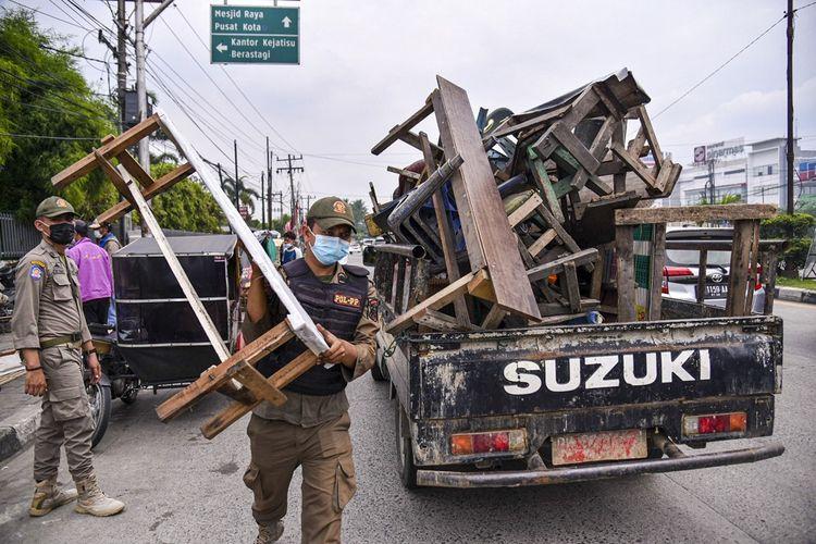 Petugas gabungan dari kepolisian dan Satpol PP mengangkut sejumlah kursi dan meja milik Pedagang Kaki Lima (PKL) yang melanggar peraturan Pembatasan Kegiatan Masyarakat (PPKM) Darurat di kawasan Medan Amplas, Medan, Sumatera Utara, Selasa (13/7/2021). Penertiban tersebut dilakukan untuk mencegah terjadinya kerumunan dan menertibkan PKL yang berjualan di bahu jalan. ANTARA FOTO/Fransisco Carolio/Lmo/aww.