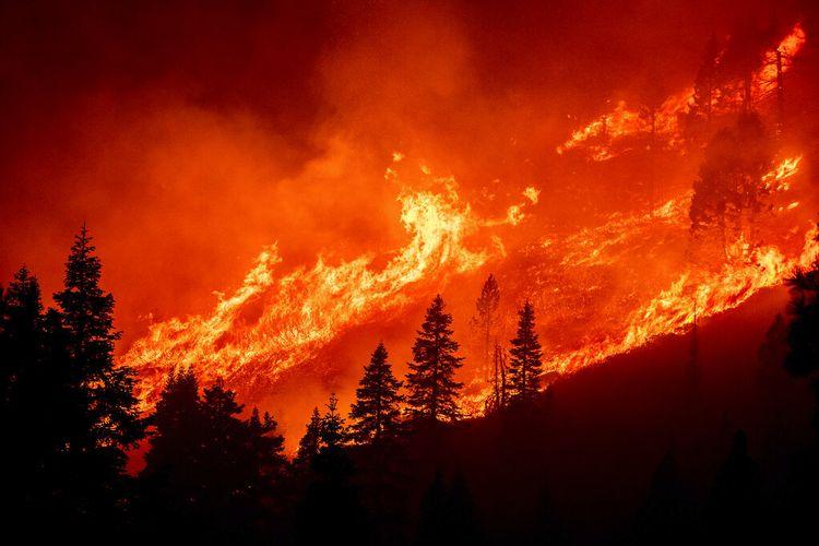 Terlihat dari South Lake Tahoe, California, kobaran api dari Caldor Fire melompati lereng bukit di atas Christmas Valley pada Senin, 30 Agustus 2021.