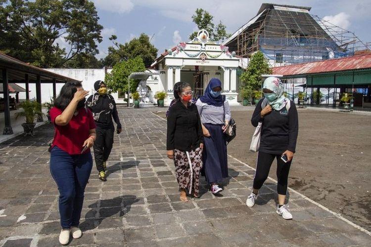 Wisatawan mengunjungi kompleks Keraton Yogyakarta, DI Yogyakarta, Selasa (14/07), yang sudah menerapkan protokol kesehatan ketat, antara lain wajib menggunakan masker.