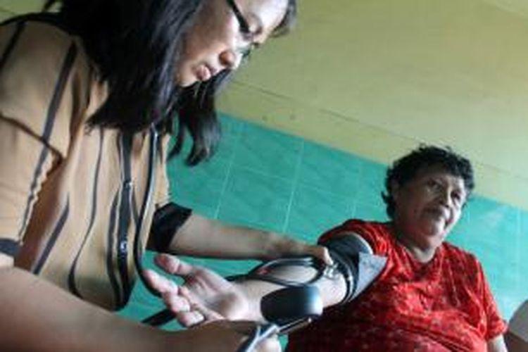 Seorang dokter sedang menangani pasien korban banjir di Manado.