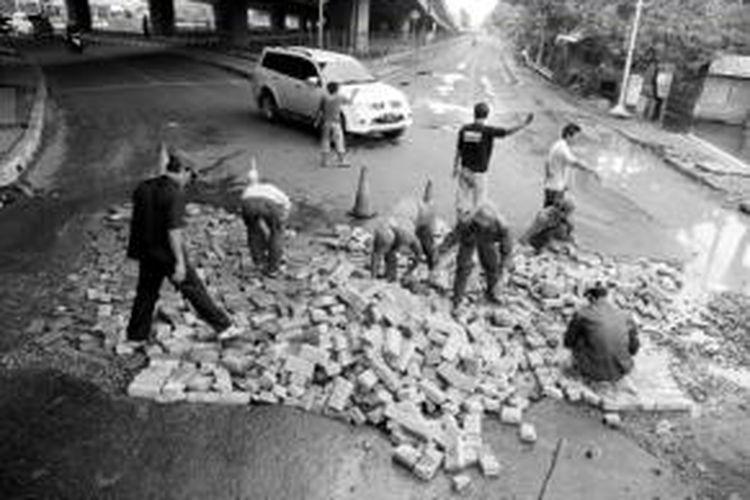 Pekerja menambal lubang besar di Jalan Puri Lingkar Luar, Puri Kembangan, Jakarta Barat, Senin (27/1). Lubang besar di jalan yang rusak itu untuk sementara ditutup dengan paving block agar kendaraan bisa melintas.