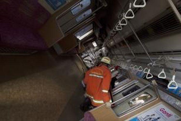 Petugas berusaha mengevakuasi korban di lokasi tabrakan kereta rel listrik (KRL) jurusan Serpong-Tanah Abang dengan truk tangki pengangkut BBM di Pondok Betung, Bintaro, Jakarta Selatan, Senin (9/12/2013). Korban tewas mendapatkan santunan hingga Rp 65 juta per orang.