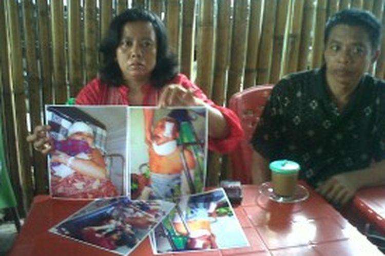 Rahmatia didampingi keluarganya memperlihatkan foto kedua orangtuanya yang menjadi korban pengeroyokan dari kedua cucunya dan rekan-rekannya saat menemui wartawan di Makassar, Minggu (23/06/2013).
