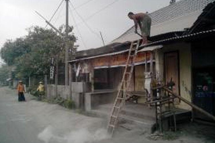 Warga di Dusun Joho,Desa Sumberejo, Kecamatan Ngasem, Kabupaten Kediri, Jawa Timur membersihkan abu vulaknik letusan Gunung Kelud, Jum'at (13/2/2014).