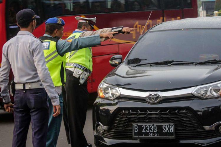 Sejumlah petugas gabungan memberi arahan kepada pengendara mobil pada uji coba ganjil genap di ruas Tol Jagorawi, Jakarta, Senin (16/4/2018). Uji coba yang dilakukan setiap hari Senin-Jumat kecuali hari libur nasional tersebut dimulai pukul 06.00 hingga 09.00 WIB diharapkan dapat mengurai kemacetan.