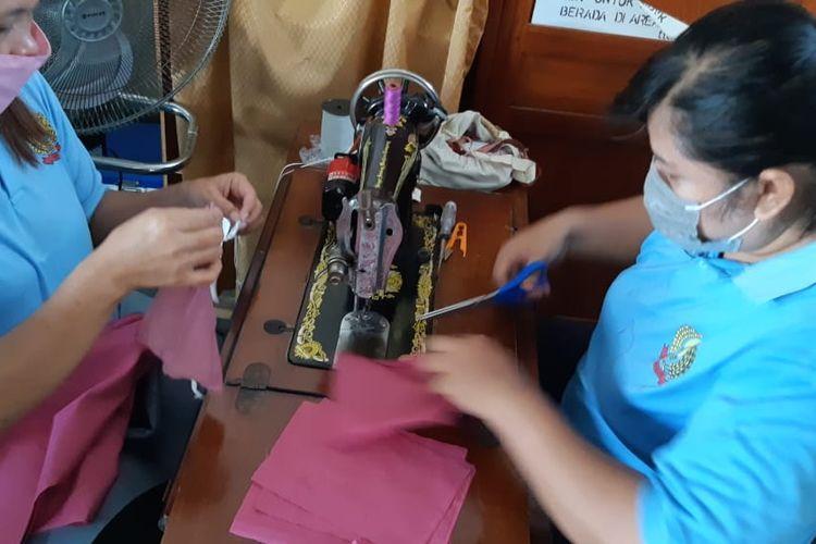 Dua orang warga binaan tengah menjahit alat pelindung diri berupa masker.