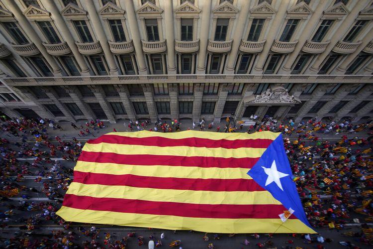 Demonstran berbaris memegang bendera pro-kemerdekaan selama Hari Nasional Catalonia di Barcelona, Spanyol, Sabtu, 11 September 2021.