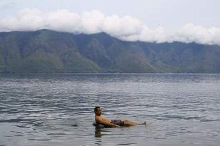 Wisatawan tengah berenang di Pantai Pasir Putih, Danau Toba, Samosir, Sumatera Utara.