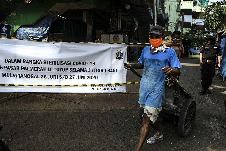 Pedagang Pasar Palmerah mengeluarkan gerobaknya dari lokasi pasar di Jakarta, Jumat (26/6/2020). Pengelola Pasar Palmerah menutup sementara pasar tersebut dari Kamis (25/6) hingga Sabtu (27/6) menyusul sembilan orang pedagang terkonfirmasi positif COVID-19 dalam tes usap yang dilakukan sebelumnya.