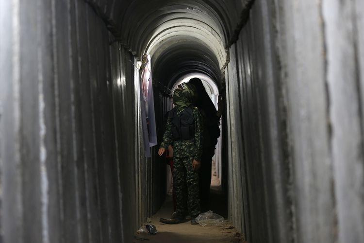 Bocah Palestina berjalan melalui terowongan yang digunakan militer selama latihan dalam eksebisi militer Hamas di Gaza pada Juli 2016.