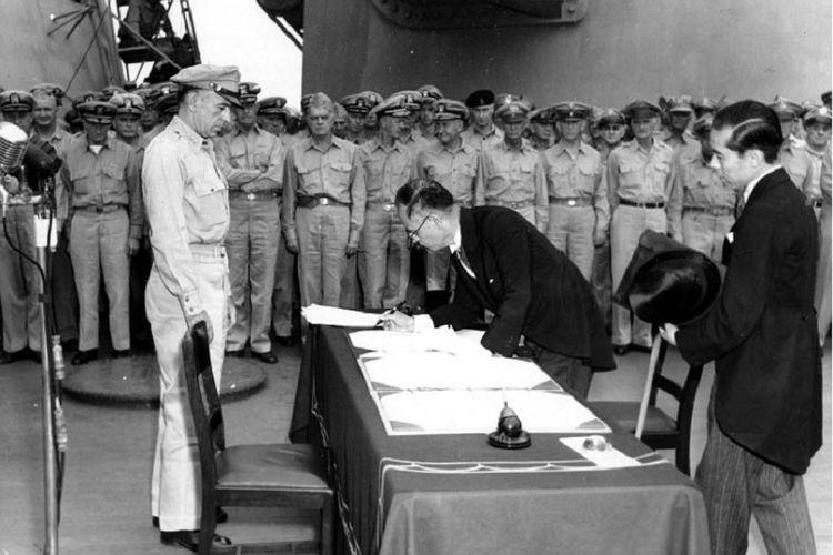 Menteri Luar Negeri Jepang Mamoru Shigemitsu menandatangani dokumen yang menyatakan penyerahan diri Jepang di geladak kapal perang USS Missouri disaksikan Jenderal Richard K Sutherland pada 2 September 1945.