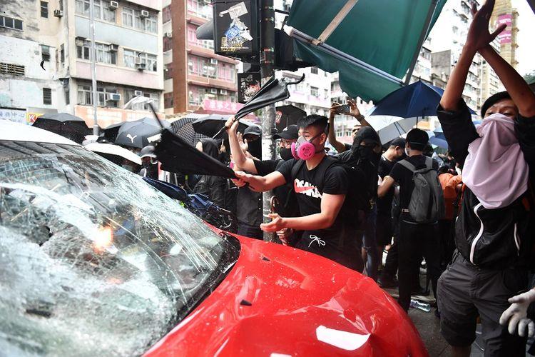Sebuah taksi menjadi sasaran kekerasan massa pengunjuk rasa setelah supirnya kehilangan kendali dan menabrak trotoar di Hong Kong, Minggu (6/10/2019).