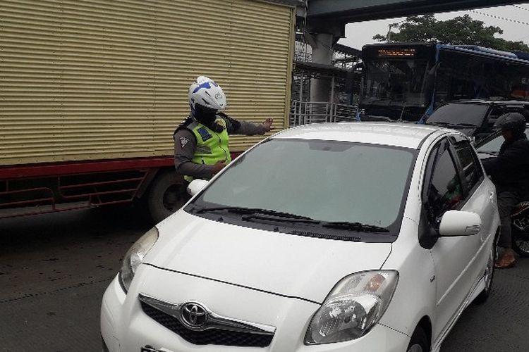 Polisi menilang sebuah kendaraan Mitsubishi Yaris warna putih dalam operasi gabungan di Jalan Daan Mogot KM 13, Jakarta Barat pada Senin (19/11/2018) sekitar pukul 09.45 WIB.
