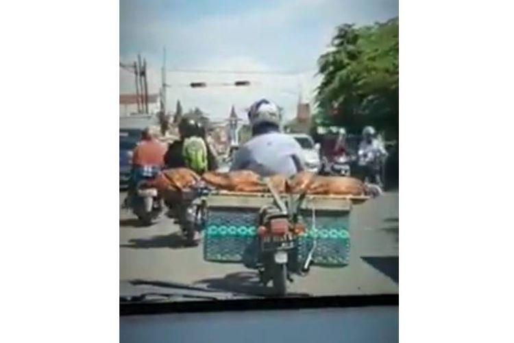 Tangkapan layar video seorang pengendara sepeda motor membawa jenazah yang terbungkus kain jarik di Boyolali, Kamis (29/10/2020).