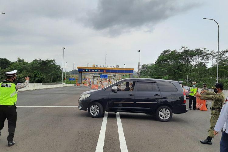 Petugas gabungan saat meminta kendaraan berplat luae kota untuk putar balik karena tidak memenuhi persyaratan untuk masuk Kota Malang terkait larangan mudik di Pintu Tol Malang, Jumat (7/5/2021)