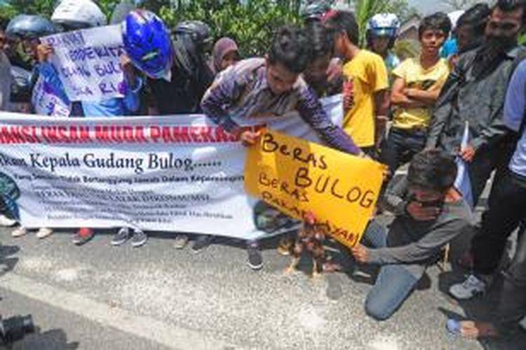 Aksi protes Raskin busuk yang dilakukan mahasiswa dan warga di depan gudang Bulog Sub Divre IV Madura, Pamekasan, Kamis (7/11/2013).