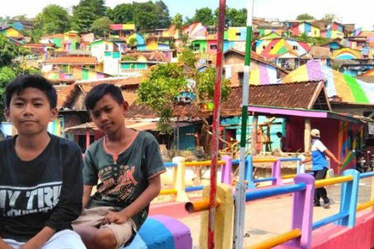 Aries Indra Kurniawan (12) bersama Maulana Gani Rauf (12) sedang duduk di jembatan yang merupakan jalan masuk Kampung Pelangi di Semarang, Jateng, seusai bermain, Kamis (26/4/2017).